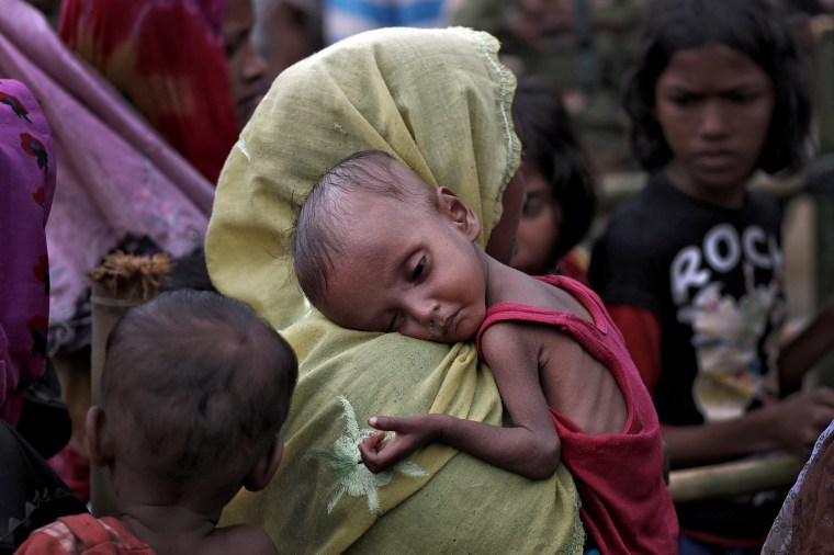Image: A woman carries an ill Rohingya refugee child through a camp in Cox's Bazar, Bangladesh
