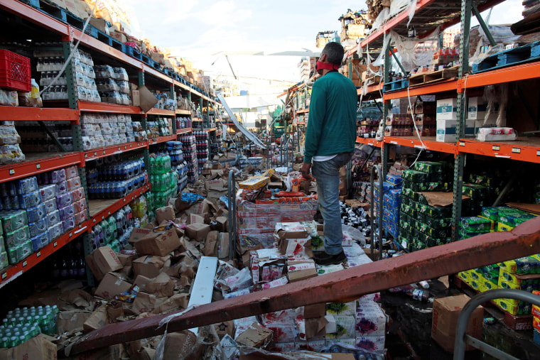 Image: A man stands inside of a destroyed supermarket by Hurricane Maria in Salinas, Puerto Rico