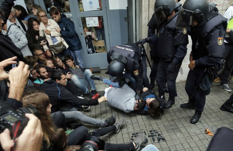Image: Police officers immobilize two people outside a polling station in Barcelona.