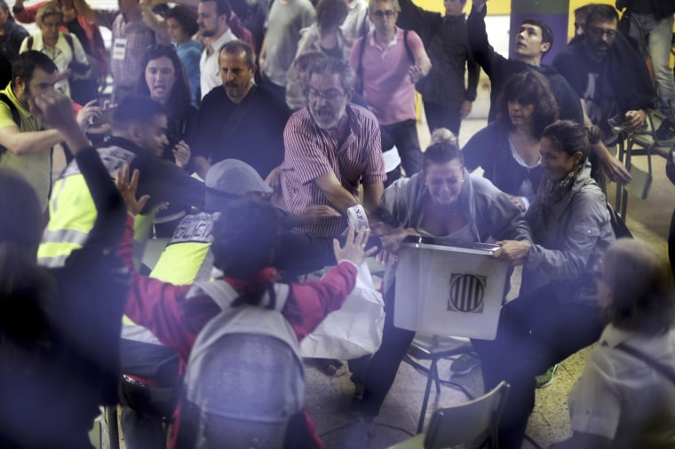 Image: Plain clothes police officers try to snatch a ballot box from polling station officials at the Ramon Llull school assigned to be a polling station by the Catalan government in Barcelona.