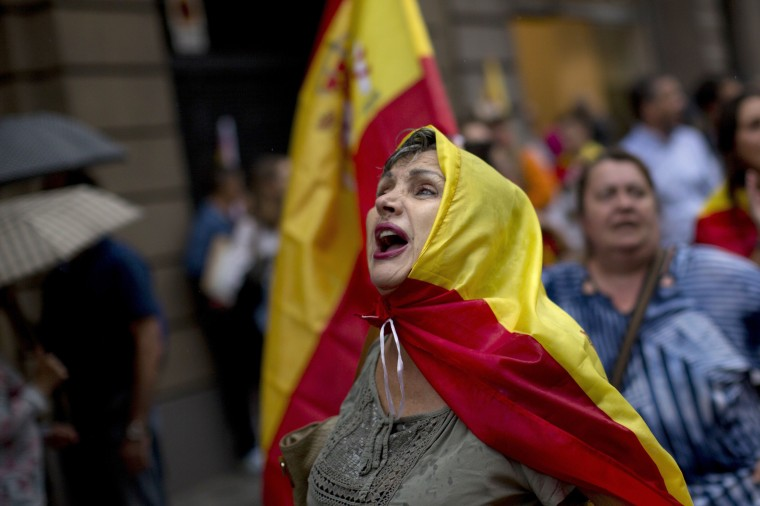 Image: Anti-independence demonstrators march through downtown Barcelona waving Spanish flags against the referendum.