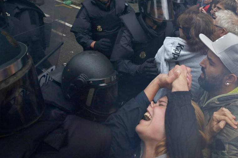 Image: A girls grimaces as a police officer pushes her away outside the Ramon Llull school.