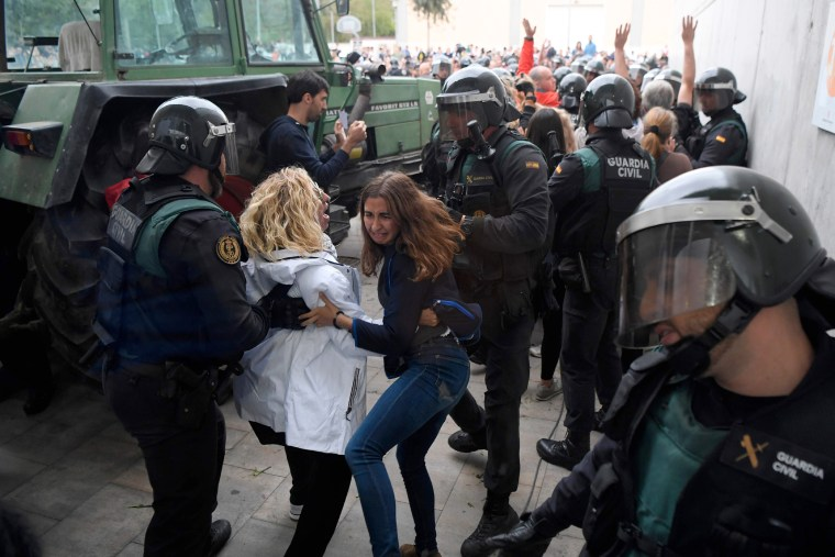 Image: Women and Spanish Guardia Civil guards clash outside a polling station in Sarria de Ter.