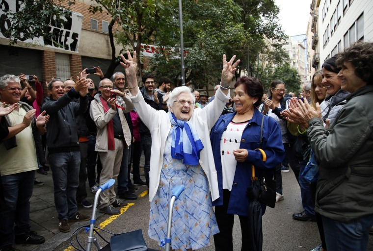 Image: An elderly woman is applauded as she celebrates after voting in the Gracia neighborhood of Barcelona.