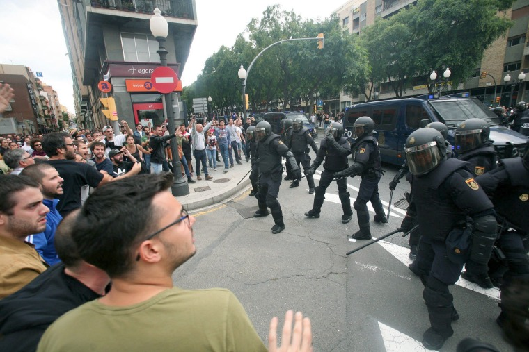 Image: Officers clash with people outside a polling center at Tarragona Secondary School in Tarragona, Catalonia.
