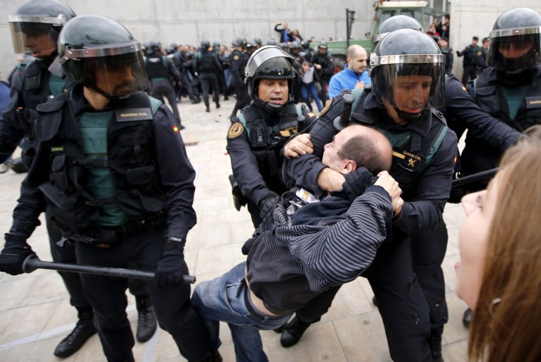 Image: Spanish Guardia Civil guards drag a man outside a polling station in Sant Julia de Ramis.