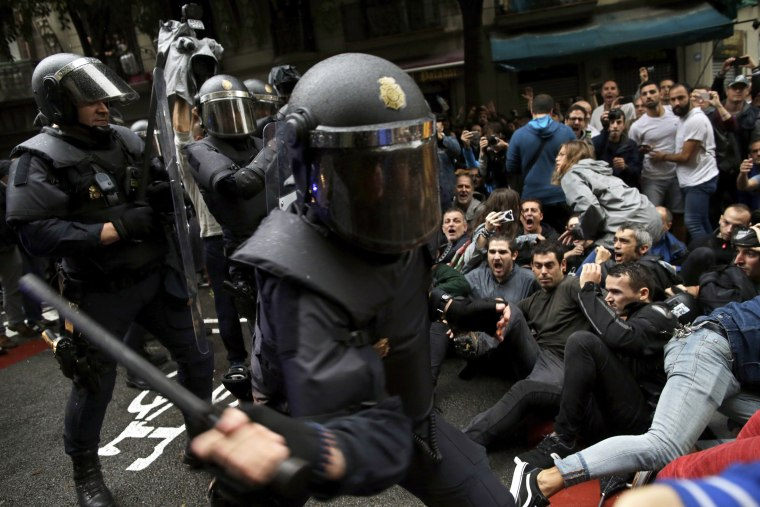 Image: Police try to remove pro-referendum supporters sitting down on a street in Barcelona.
