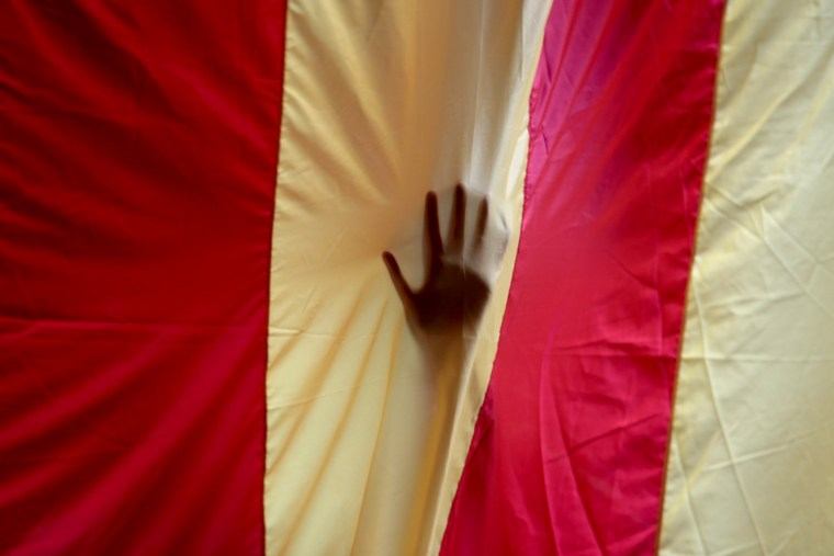 Image: A hand is seen through a giant Estelada in the University of Barcelona's historic building.