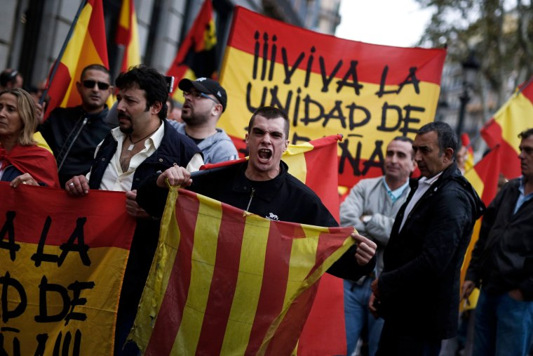 Image: A protester shouts as he holds a Catalan flag during a far-right demonstration.