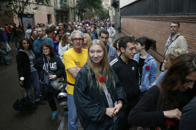 Image: People wait outside a polling center in the Gracia neighborhood of Barcelona.
