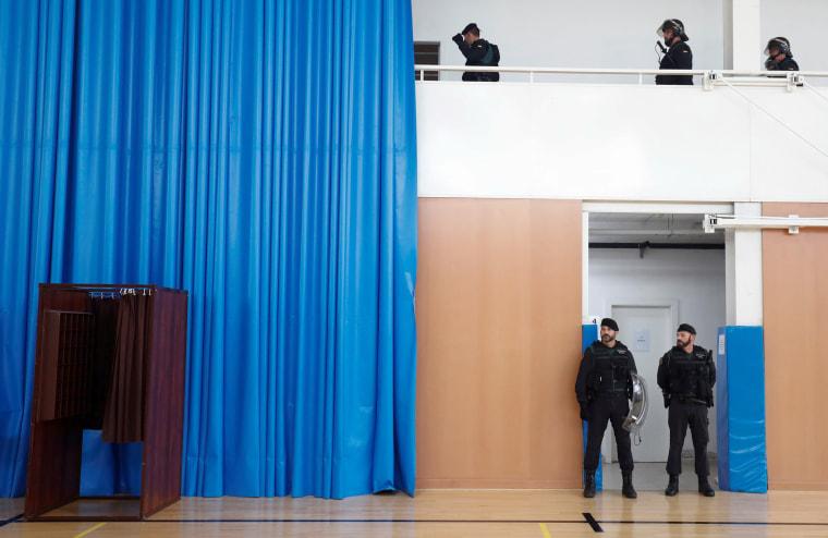 Image: Civil Guard officers stand inside a polling station for the banned independence referendum where Catalan President Carles Puigdemont was supposed to vote in Sant Julia de Ramis.