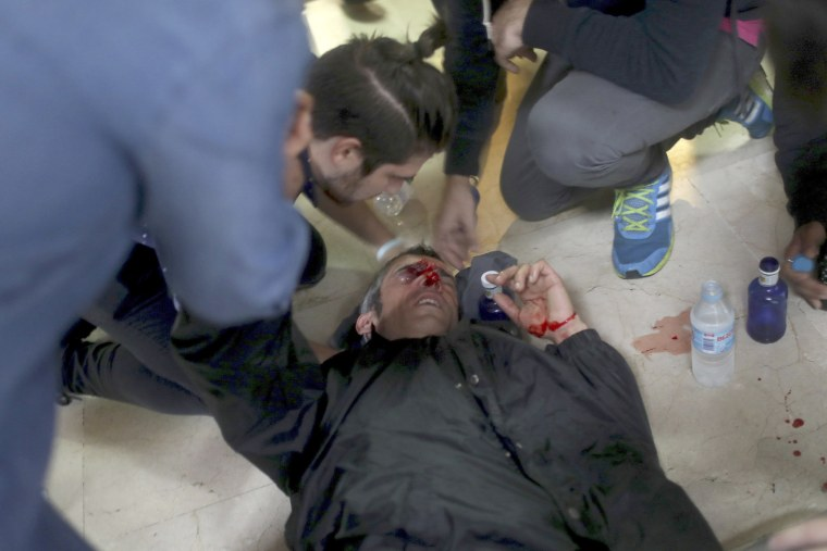 Image: A protester is attended to after being hit by a rubber bullet shot by Spanish National Police near the Ramon Llull school.