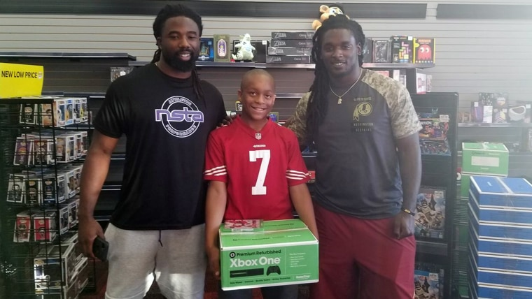 A little boy who went to a Game Stop and walked out with an Xbox courtesy of two sweet NFL football players