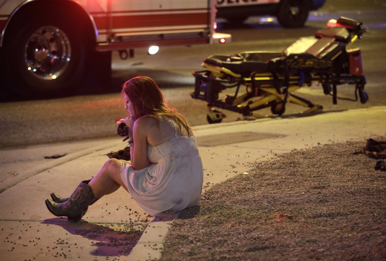 Image: A woman sits on a curb at the scene of a shooting in Las Vegas