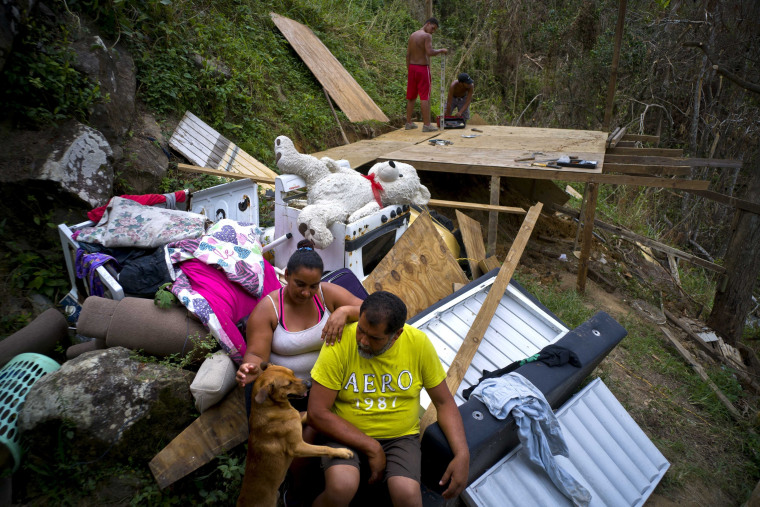 "Yadira Sortre and William Fontan Quintero pose to what is left of their belongings, destroyed by Hurricane Maria while their children build a room to protect themselves from the elements, in the San Lorenzo neighborhood of Morovis, Puerto Rico, Saturday, Sept. 30, 2017.  ""We lost everything,"" Fontan said. They have three children, one lives in Chicago and two live with them in Puerto Rico."