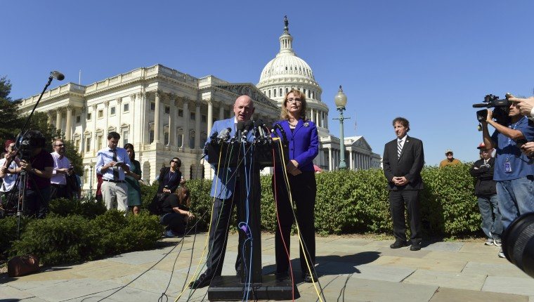 Image: Former Rep. Gabrielle Giffords, D-Ariz., right, listens as her husband Mark Kelly speaks on Capitol Hill