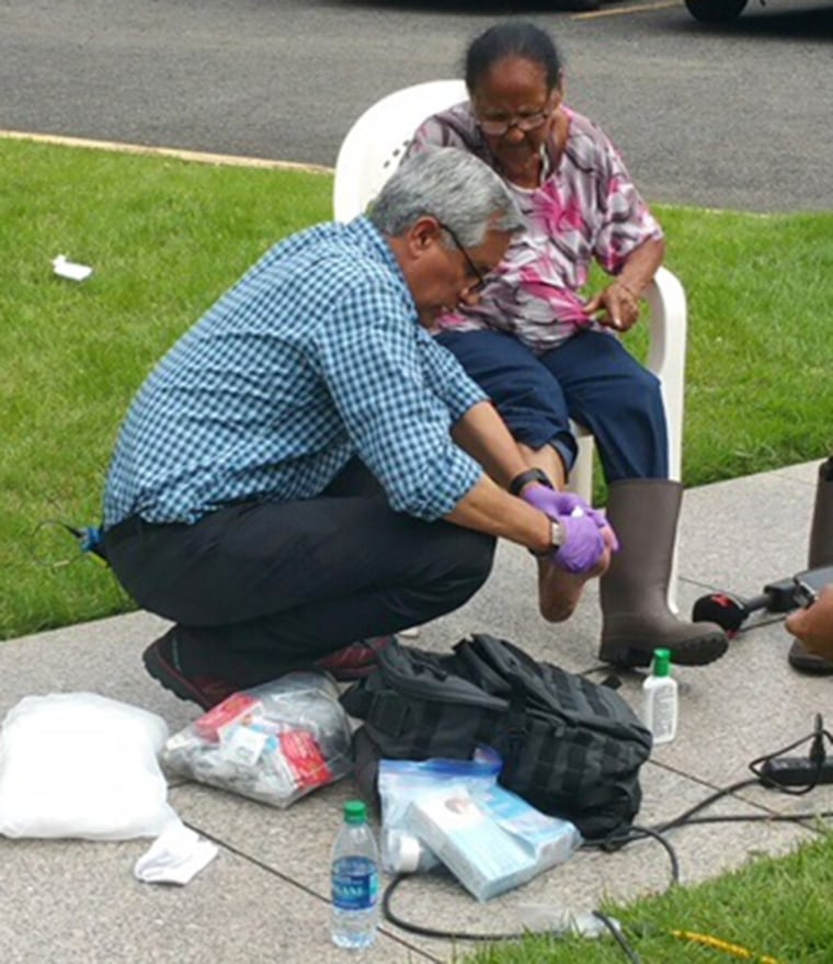 Dr. John Torres, NBC News Medical Corresopondent, treats a wound on Ana Maria Ortiz's foot. The Puerto Rican native has been waiting to see a doctor since Hurricane Maria hit 14 days ago.