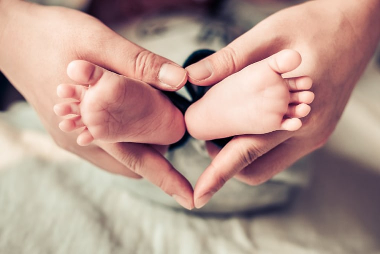 Image: Mom holding babies feet