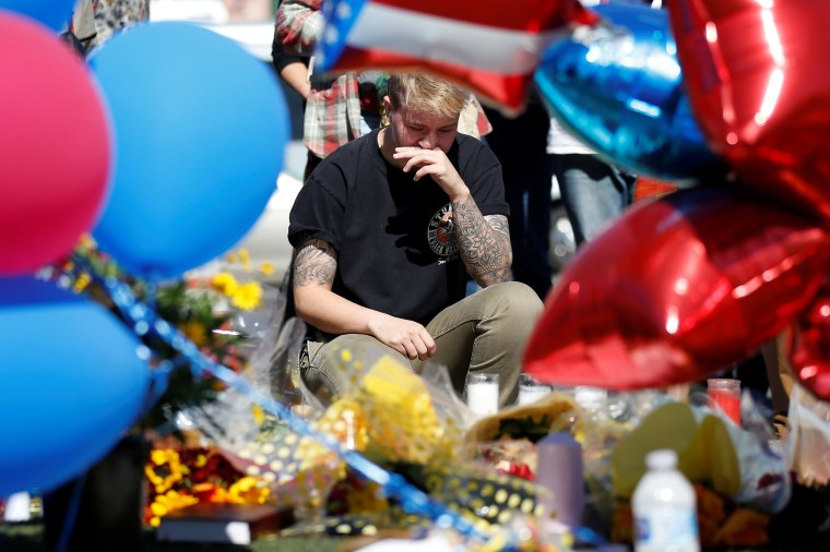 Image: Bry Thompson wipes away tears at a makeshift memorial in the middle of Las Vegas Boulevard following the mass shooting in Las Vegas