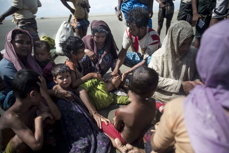 Image: Rohingya Muslim refugees exhausted by their journey rest upon arrival on the Bangladeshi shoreline