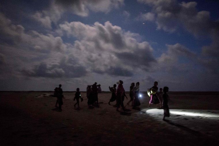 Image: Rohingya Muslim refugees walk by night after crossing the border from Myanmar