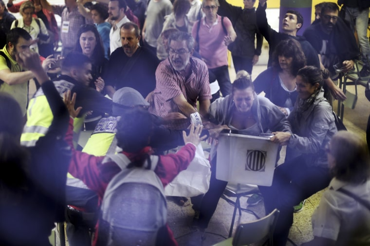 Image: Spanish National Police officers in plain clothes try to snatch a ballot box from polling station officials