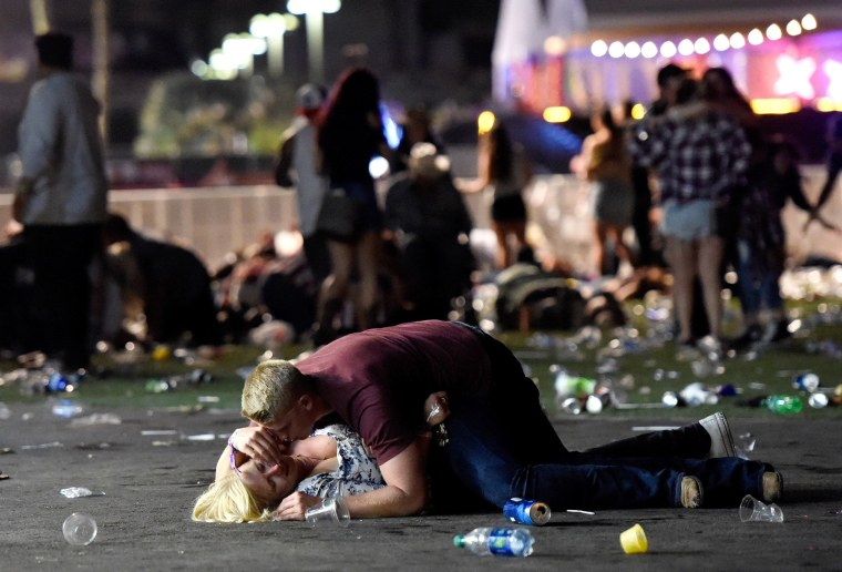 Image: A man lays on top of a woman after a shooting in Las Vegas