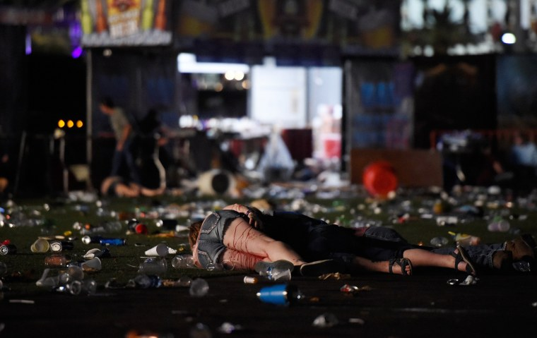 Image: A person lies on the ground covered with blood at the Route 91 Harvest country music festival