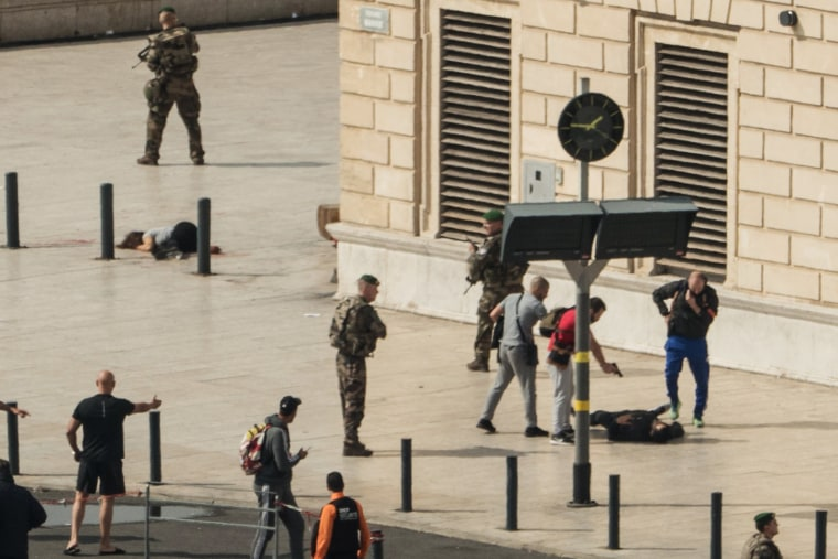 Image: French police point a gun at a man on the ground after a woman was stabbed in Marseille