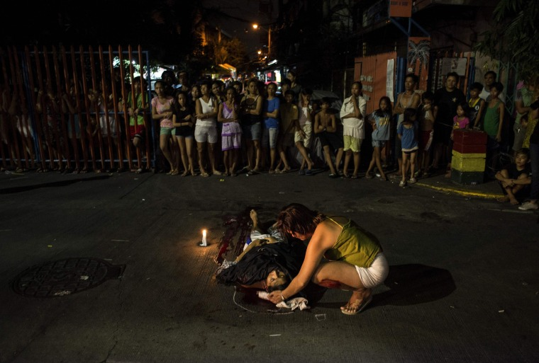 Image: Nanette Castillo looks at the dead body of her son