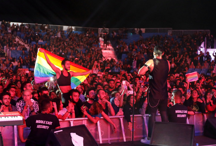 Image: FILE PHOTO:A fan of Lebanese alternative rock band Mashrou' Leila holds a rainbow flag during their concert at the Ehdeniyat International Festival in Ehden town