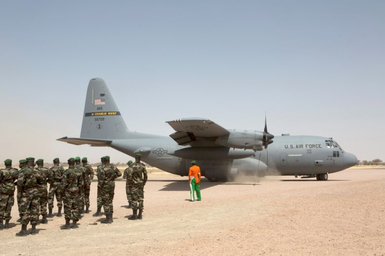 Image: A C-130 U.S. Air Force plane lands as Nigerien soldiers stand in formation during the Flintlock military exercise in Diffa, Niger March 8, 2014.