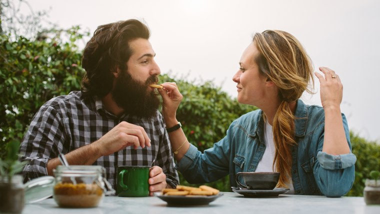 Young couple feeding each other biscuits in garden