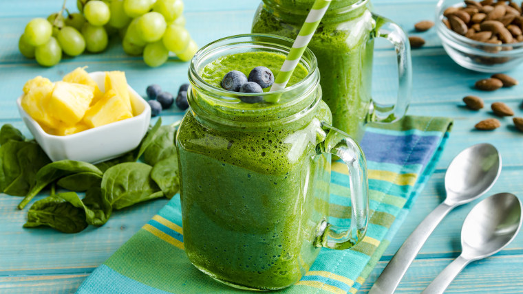 Mason jar mugs filled with green spinach and kale health smoothie with green swirled straw sitting with blue striped napkin and spoons; Shutterstock ID 380369794; Purchase Order: -