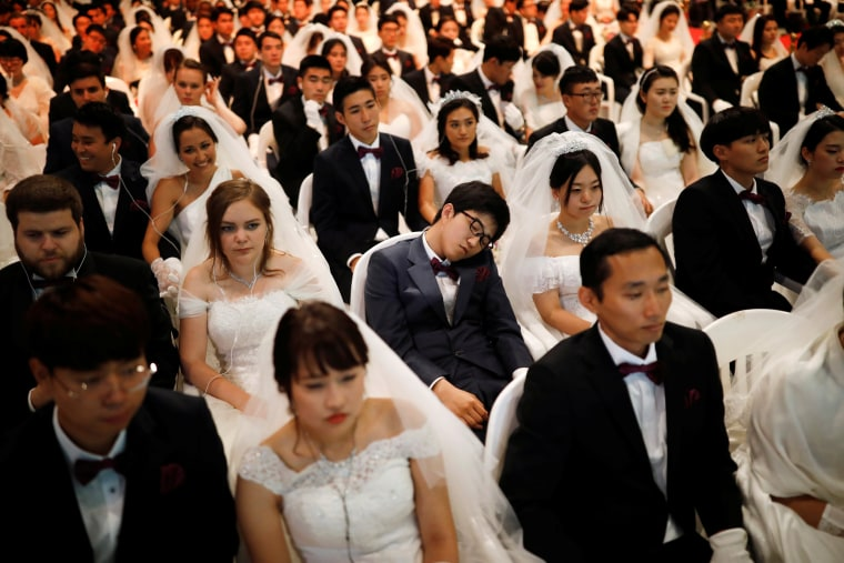 Image: A groom naps as newlywed couples attend a mass wedding ceremony of the Unification Church at Cheongshim Peace World Centre in Gapyeong