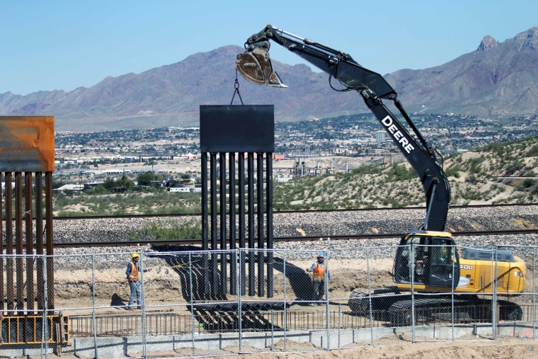Image: Workers operate a crane on the last section of the metal barrier between the cities of Ciudad Juarez