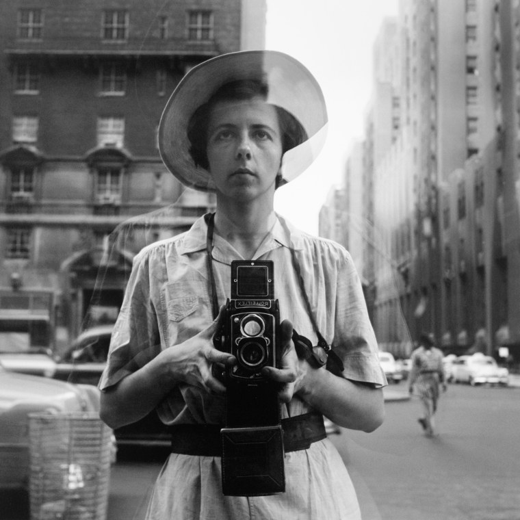 Image: Maier in a self-portrait as she looks into a storefront in New York.