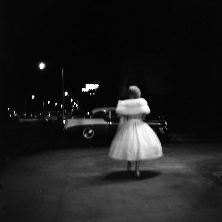 Image: A woman in a party dress walks towards a car in Miami, 1957.