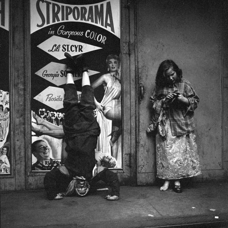 Image: A man does a headstand in front of a poster advertising a strip show in New York, 1953.