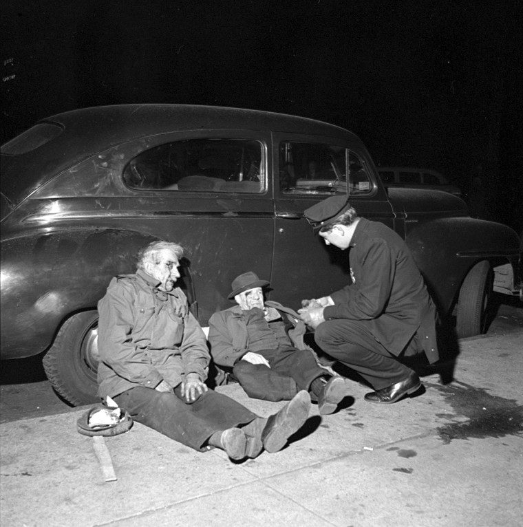 Image: A police officer arrests two suspects on Christmas Eve in New York, 1953.