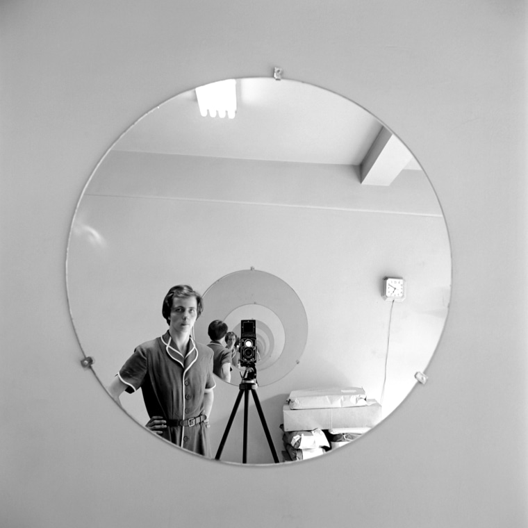 Image: Maier in a self-portrait in a round mirror in New York, 1955.