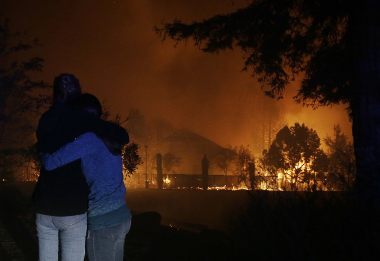 Image: Two people hug as they watch houses burn in Santa Rosa