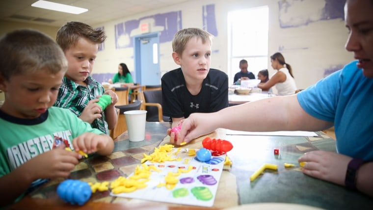 Ayden, 9, plays a board game with other children at the Children's Home Network.