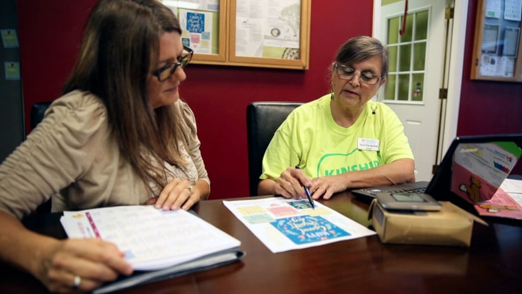 "Tena Randecker, right, walks Rebecca Schuckert, 54, through programs available to her grandchildren. Randecker is raising her own grandchildren and now helps other grandparents as a Kinship Navigator with the Children's Home Network. ""We need the caregivers to know they aren't alone,"" she said."