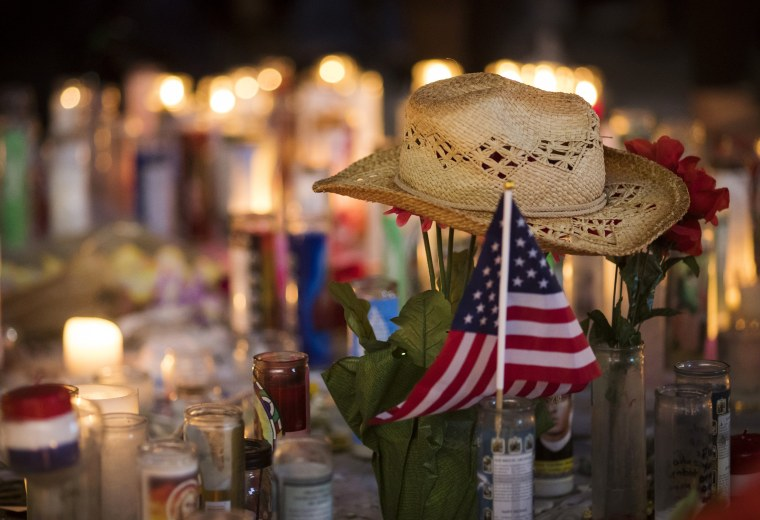 Image: A hat is left at a makeshift memorial during a vigil