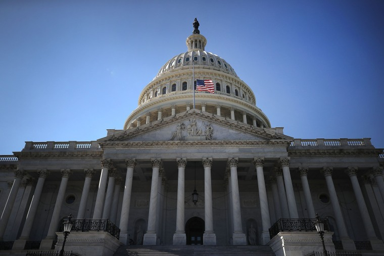 Image:  An American flag flies at half-staff at the U.S. Capitol