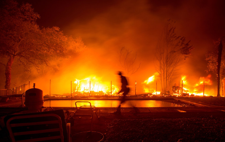 Image: A firefighter walks near a pool as a neighboring home burns