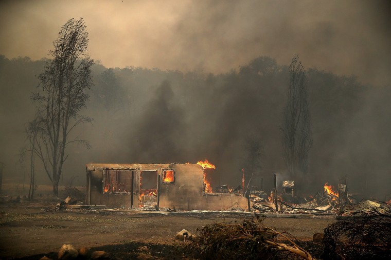 Image:  Fire consumes a house as an out of control wildfire moves through the area