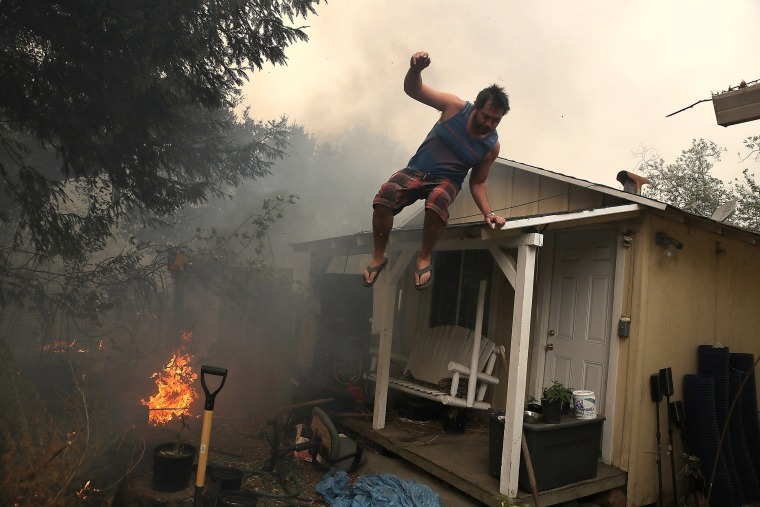 Image: A resident rushes to save his home as an out of control wildfire moves through the area