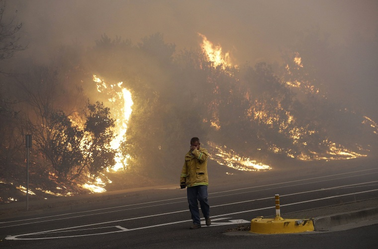 Image: A firefighter covers his eyes as he walks past a burning hillside in Santa Rosa